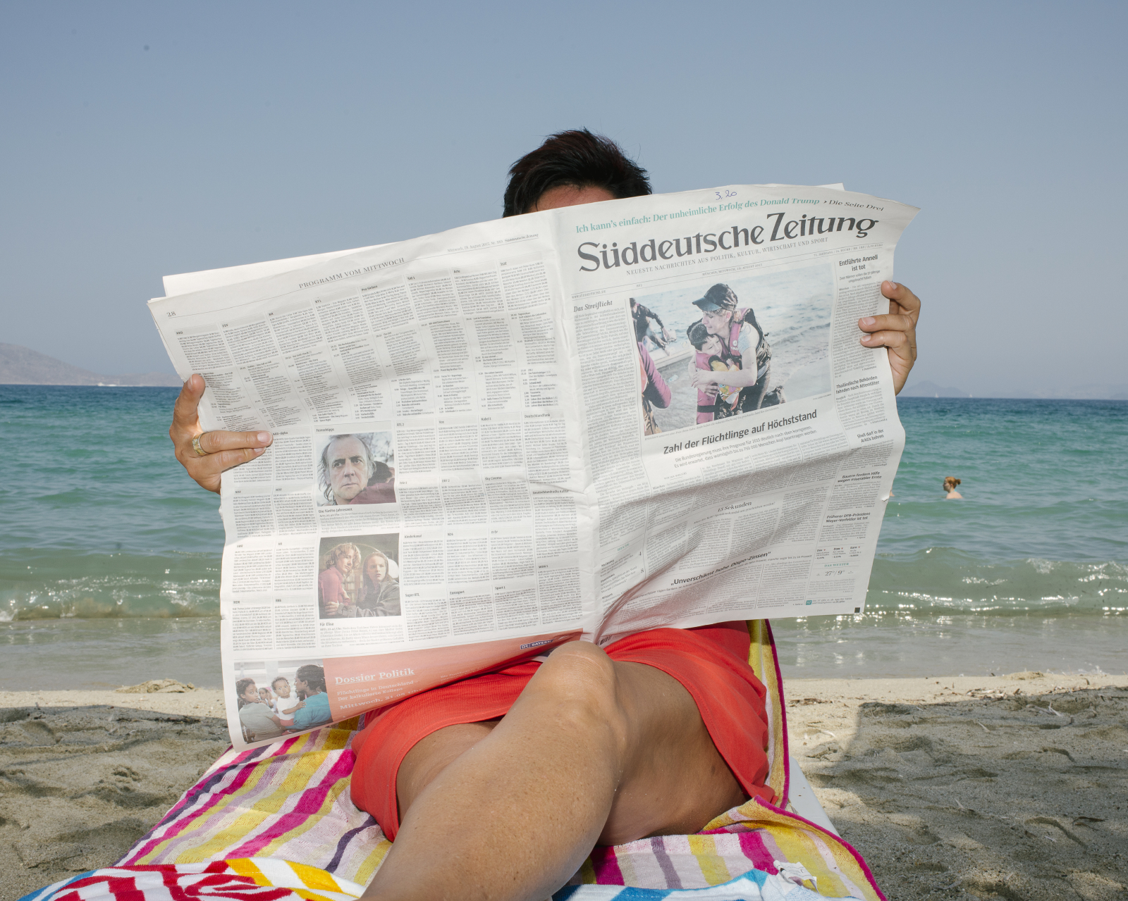 Tourist reading the newspaper on the beach, August 2015, Kos, Kos Island, Greece, Europe